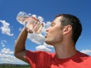Man drinking water against blue sky